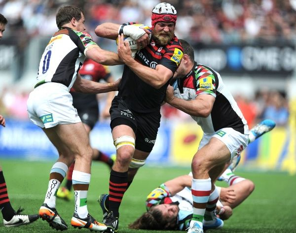 Saracens' Alistair Hargreaves is tackled by Harlequins' Nick Evans (left) and Nick Easter (right) during the Aviva Premiership Play-off, Semi Final match at Allianz Park, London