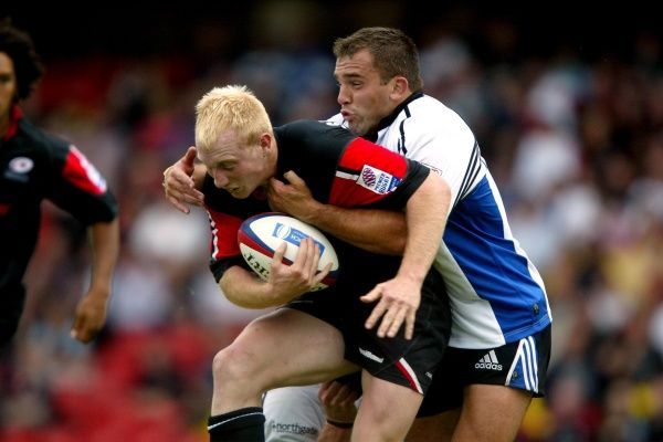 (L-R) Saracens' Tom Shanklin is tackled by Bath's Simon Emms
