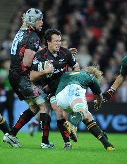 Saracens' Derick Hougaard tackled by South Africa's Dewald Potgiete