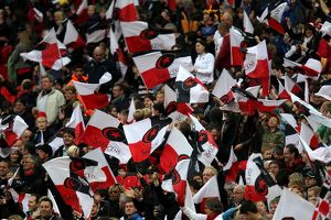 Saracens fans show their support in the stands by waving flags